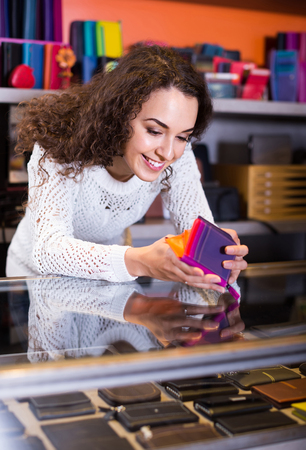 Happy young brunette choosing purse with many sections in store