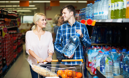 still water: Young smiling customers choosing bottle of still water at store Stock Photo