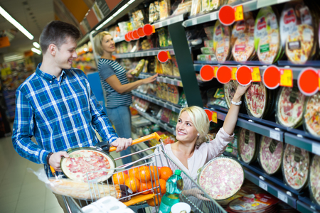 cooled: Happy young couple choosing Italian pizza in cooled food section. Focus on girl Stock Photo