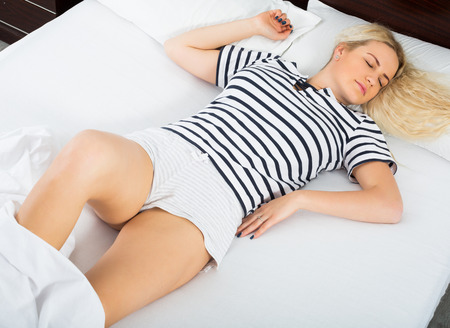 early 30s: Young girl taking nap in bedroom interior