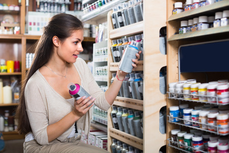 aerosol can: portrait of young cheerful woman choosing paint color in aerosol can in art shop
