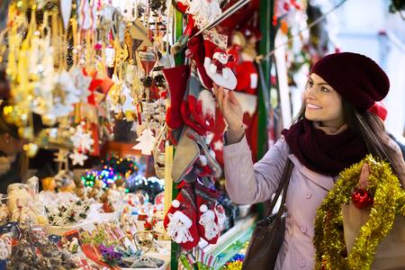 Portrait of smiling  girl shopping at festive fair before Xmas