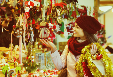Young happy woman shopping at festive fair before Christmas