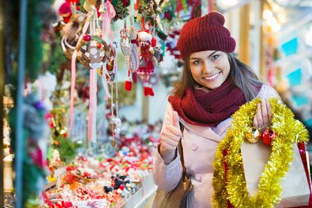 Beautiful happy smiling woman choosing Christmas decoration at market