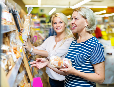 provision: Mature woman choosing a pastry in bakery section of supermarket
