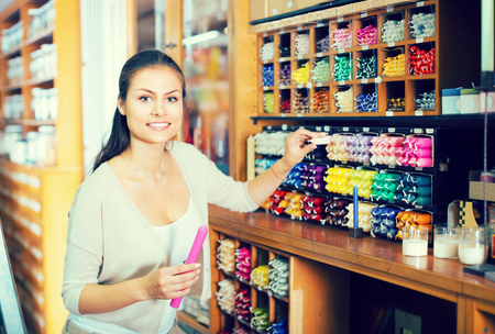 chandler: young glad woman holding multicolored candles in hands in craft department