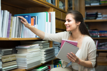 writing paper: ?Young smiling woman shopping notebooks and writing paper in stationary store