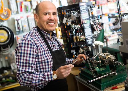 Joyful smiling mature man in apron working in locksmith and making duplicates of keys Reklamní fotografie