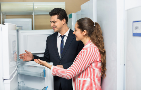 domestic appliances: Satisfied customers looking at large fridges in domestic appliances section