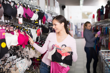brassiere: Young woman holding different brassiere in hands in underwear store Stock Photo
