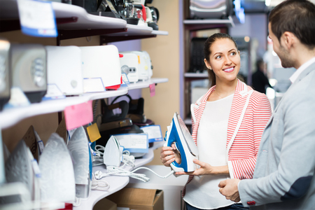 choosing clothes: Positive young couple choosing clothes iron in hypermarket and smiling Stock Photo