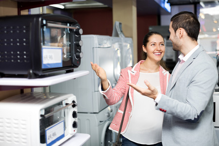 Smiling family couple choosing new microwave in supermarket. Focus on the woman Imagens