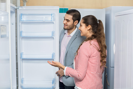 domestic appliances: Satisfied happy customers looking at large fridges in domestic appliances section Stock Photo