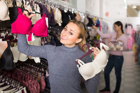 Cheerful young woman shopping lace uplifts in lingerie department Stock Photo