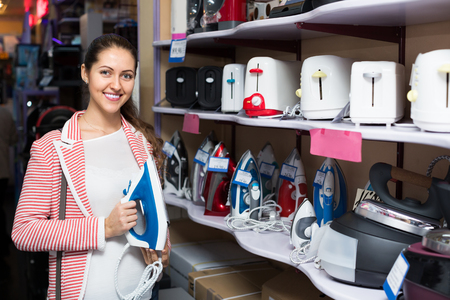 domestic appliances: Positive female customer looking at irons in domestic appliances section