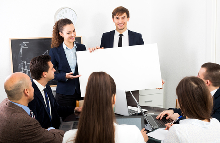 new development: Positive young businessman presents new development plan at poster Stock Photo