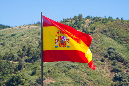 Spanish tricolour fluttering on wind, mountains at the distance
