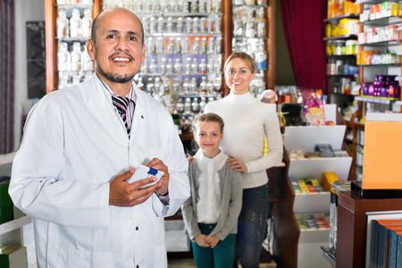 diligente: Madura sonriente c�moda farmac�utico de sexo masculino diligente en la capa blanca que trabaja la tienda farmac�utica y la consulta de los clientes