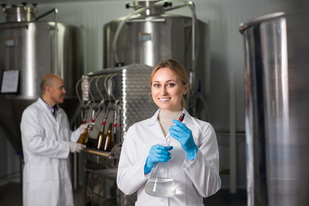 technologist: Smiling young female technologist and male worker bottling beer at  brewery factory Stock Photo