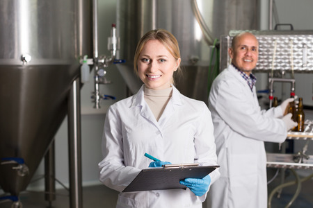 production facility: Portrait of adult woman employee in modern beer production facility Stock Photo