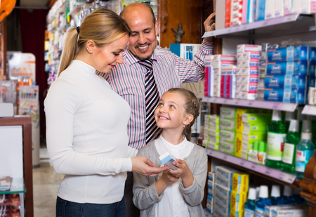 Cheerful smiling family of three persons picking items in the pharmacy Stock Photo