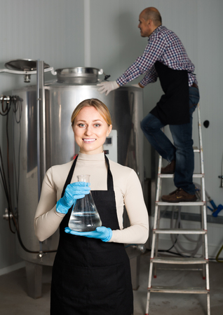 production facility: Portrait of glad woman employee in modern beer production facility
