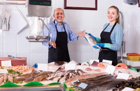 Fisch und Meeresfrüchte-Geschäft mit zwei positiven Verkäufer in Schürzen an der Theke lächelnd Standard-Bild