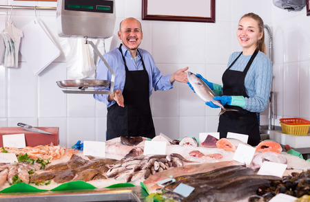 Fish and seafood store with two positive smiling sellers in aprons at the counter Stock Photo