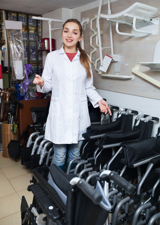 orthopaedic: Positive female consultant selling wheelchairs in special store with orthopaedic equipment Stock Photo