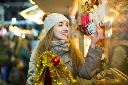 Portrait of happy russian smiling woman in coat posing at Xmas fair in evening