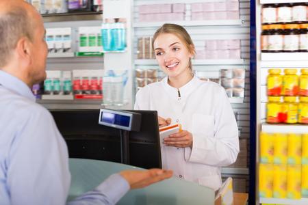 Pharmaceutist in drugstore helping customer to choose medication