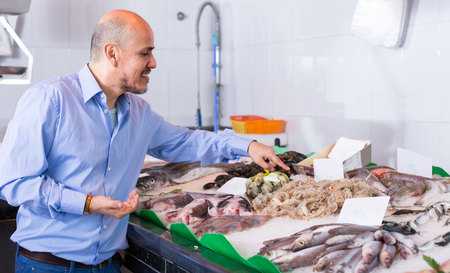 cooled: Mature man in casual selecting cooled fish at fishery Stock Photo