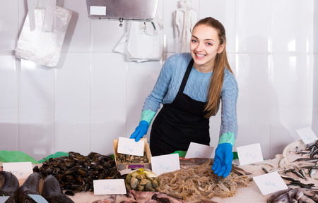 shopgirl: smiling shopgirl with apron offering fresh fish in shop Stock Photo