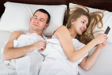 Positive girl chatting with mobile, man sleeping by in bed