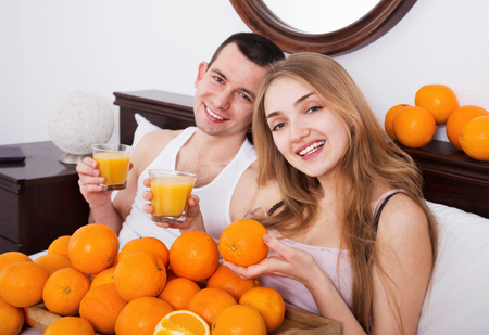 squeezed: Pleasant smiling couple with ripe oranges and freshly squeezed juice Stock Photo