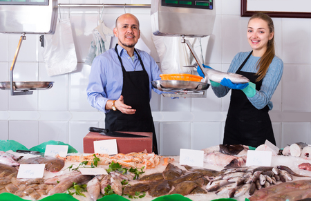 Shopgirl and salesman posing near display with frozen fish