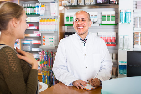 druggist: Cheerful male pharmacist serving young woman in pharmacy and smiling