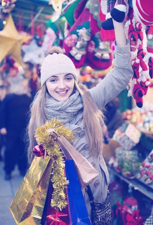 spanish woman: Portrait of positive spanish woman in coat posing at Xmas fair in evening
