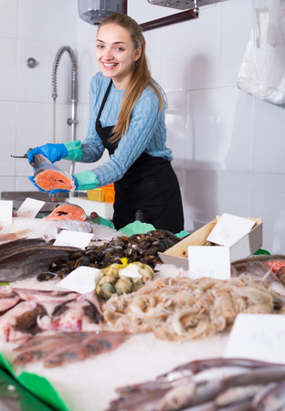 smiling girl posing near display with cooled fish and seafood