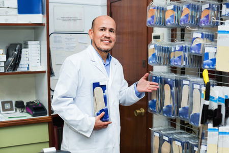 Elderly professional consultant offering orthopaedic insoles in store and smiling