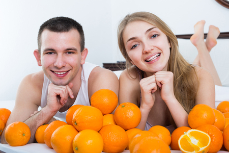 Positive couple lying in bed with orange fruits