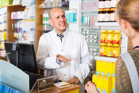 farmacy: Experienced pharmacist counseling woman in modern farmacy Stock Photo