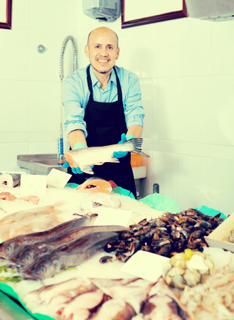 fish selling: Smile man selling frozen fish and seafood in store