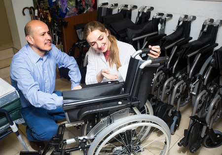 orthopaedic: Smiling  female consultant offering manual wheelchairs to customer in orthopaedic store