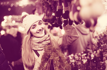 lifestile: Portrait of smiling longhaired girl near counter choosing Christmas gifts at market in evening time