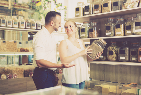 shopping questions: happy smiling young couple choosing herbs and spices in organic food store