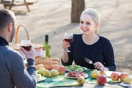 curare teneramente: happy american couple drinking wine and talking on picnic Archivio Fotografico