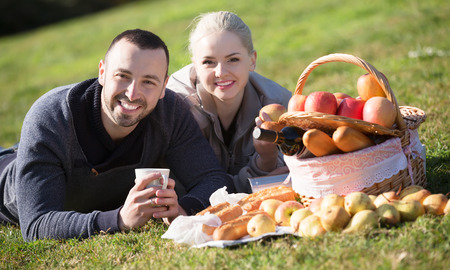 sandwitch: Young couple lounging in sunny spring day at picnic outdoors and smiling