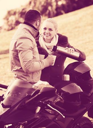 젊은 미소 커플 sandwitch 및 커피와 오토바이 근처 포즈