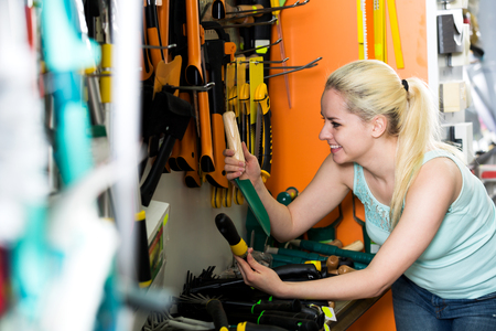 horticultural: Young blond woman picking various horticultural sundry in household shop